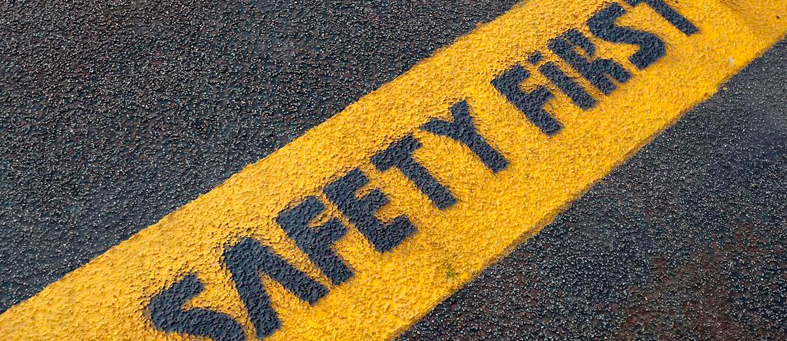 "Close up of ""Safety First"" written on asphalt in yellow bar"